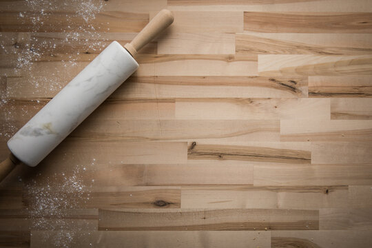High Angle View Of Table, Flour And Marble Rolling Pin