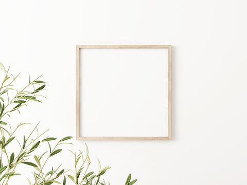Square wooden frame mockup with green olive tree branches on empty white wall background. 3D rendering, illustration