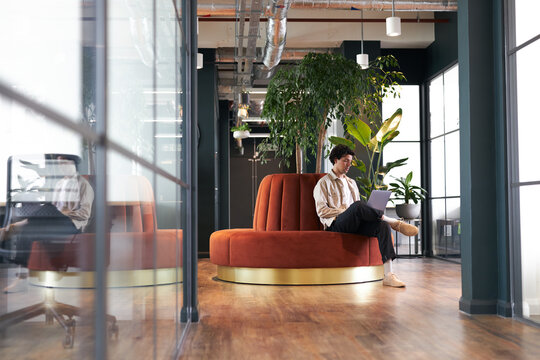 Young man with laptop in seating area of open plan office renting work space for start up business