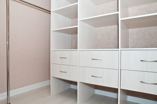 A fragment of the interior of the dressing room with drawers, shelves and rods for hangers