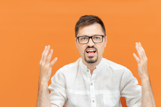 What do you want from me. Nervous disappointed brunette man in white shirt spreading hands being in uncomfortable situation. Portrait of irritated angry man. Studio shot isolated on orange background