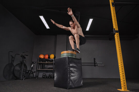 Crossfit athlete doing box jump exercise as part of functional circuit training at dark gym. Strong shirtless fit muscular man performing box jump hardcore workout for legs. Crossfit, fitness, workout