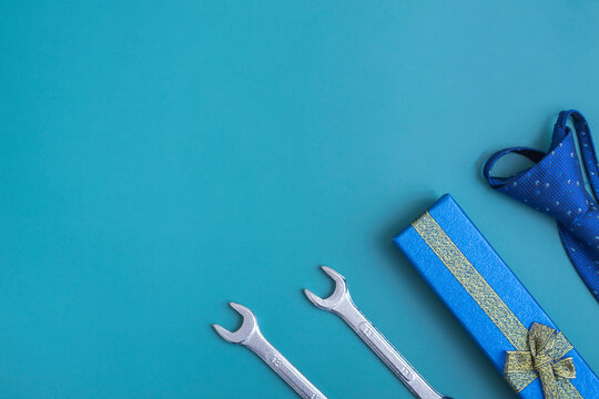 Father's day. Flat lay of gift box, tools and blue tie on blue background. Top view, copy space. Father's day concept