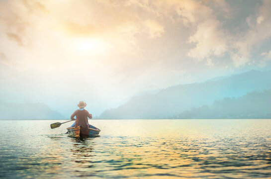 Back view of lonely fisherman in boat on morning lake