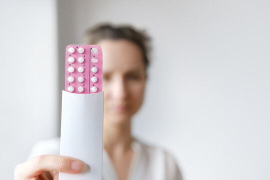 Unrecognized woman in white blouse holding hormonal oral contraceptives in a pink blister. Concept of Hormonal methods of birth control. Estrogen and Progestin hormonal balance.
