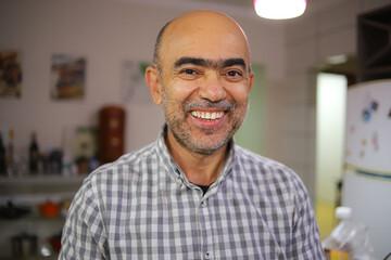 Obraz Homem de acima de 50 anos, sorrindo, de camisa xadrez, dentro de uma cozinha. - fototapety do salonu