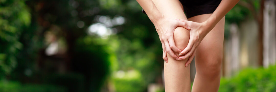 woman pain knee at the park