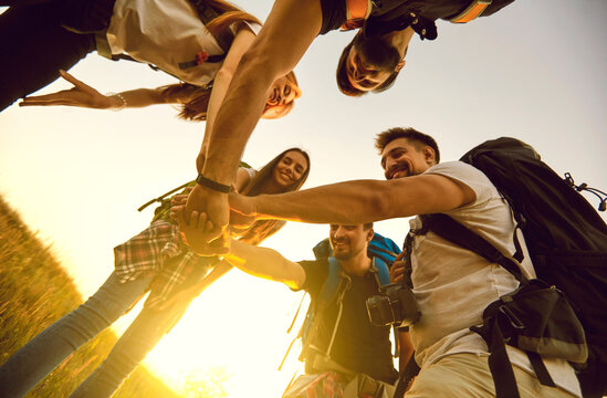 From below of a team of happy young friends joining hands ready for great travel adventure. Low angle of group of tourists with backpacks stacking hands in summer field while hiking in countryside
