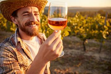 Fototapeta Happy winemaker with glass of wine in vineyard obraz