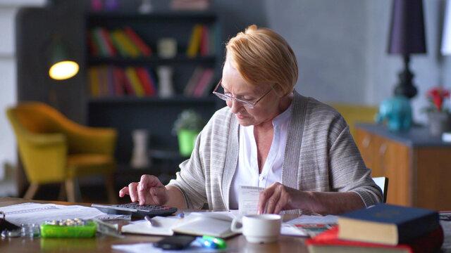 Senior business woman holding paper bill using calculator