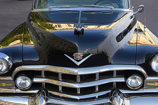 ST. PETERSBURG, RUSSIA - JUNE 9, 2021:  Cadillac Coupe Deville 1950s, black executive car, old classic retro auto, era of great gatsby, city reflections on a shiny car bodywork