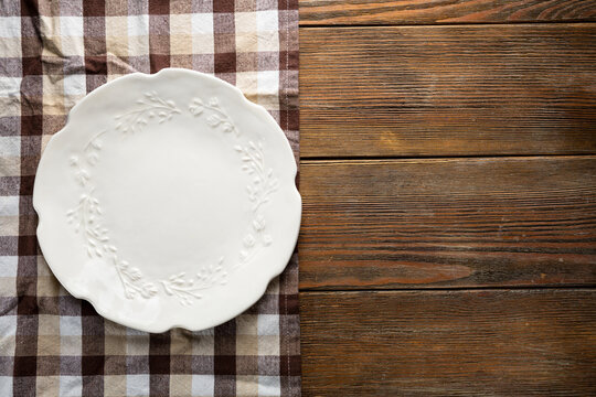 Overhead view of empty white plate on wooden table