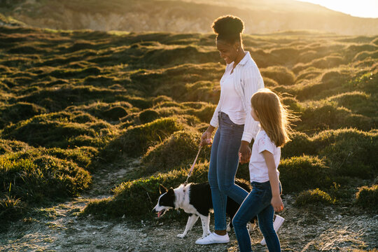 Black woman with kid and dog walking in nature