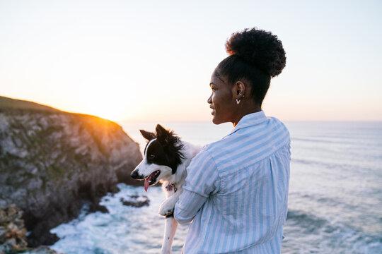 Happy black woman having fun with dog on beach