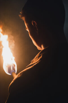 Man with burning fire in dark cave