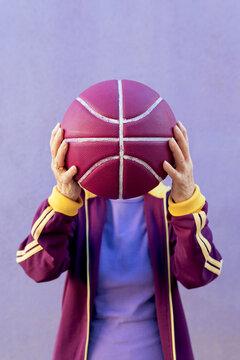 Unrecognizable elderly athlete with basketball on violet background