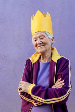 Senior sportswoman in paper crown with crossed arms
