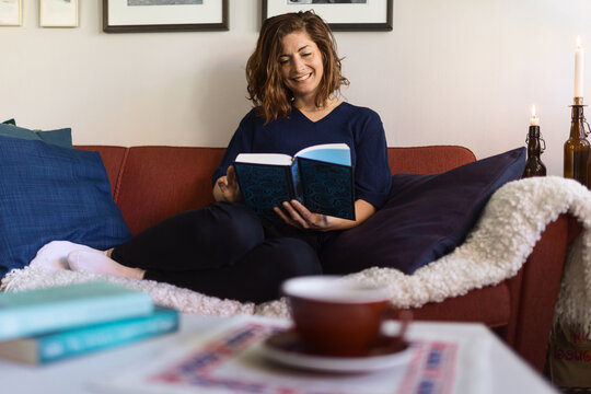 Dreamy woman reading book on sofa