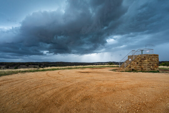 Dark cloud formations over a raised stone lookout platform