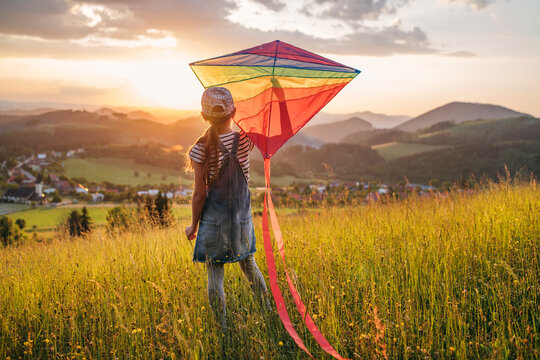 Little girl enjoying the sunset on the meadow grass and preparing colorful rainbow kite toy for flying. Happy childhood moments or outdoor time spending concept image.