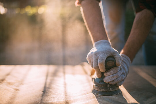 A male carpenter works with a wood grinder. Close-up. Professional equipment and protective equipment.