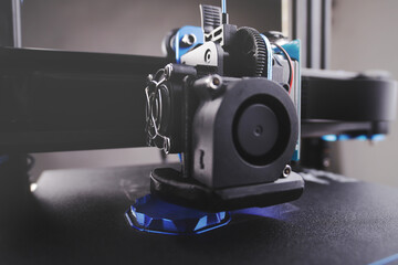 Obraz black FDM 3D printer manufactures a hollow part from metallic blue plastic in thick layers - additive manufacturing concept with selective focus - fototapety do salonu
