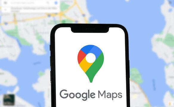 Google Maps Logo mit Schriftzug auf einem Smartphone angezeigt, im Hintergrund eine Kartenansicht von Google Maps