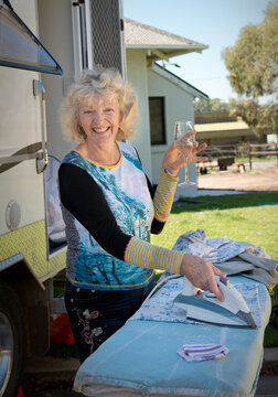 Retired woman ironing outside her caravan with a glass of wine