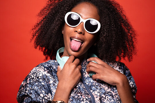 Stylish black woman with headphones on red background