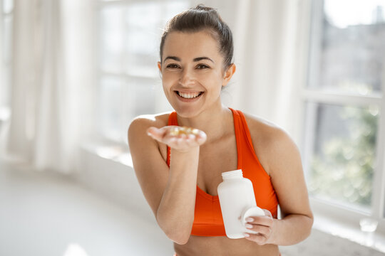 Portrait of a cheerful woman taking supplements or vitamins in the form of capsules after training in the gym. Concept of additional nutrition during training