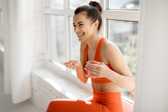 Happy woman takes supplements or vitamins in the form of capsules after training in the gym. Concept of additional nutrition during training