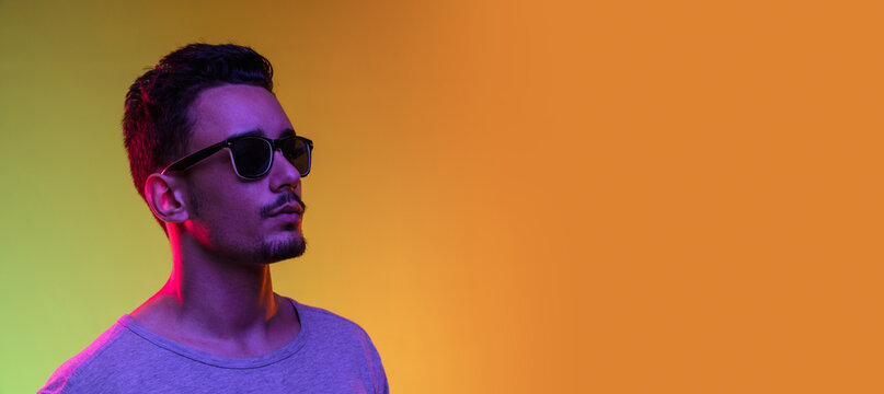 Portrait of Latina young man in sun glasses posing isolated on gradient yellow green background in neon light. Flyer