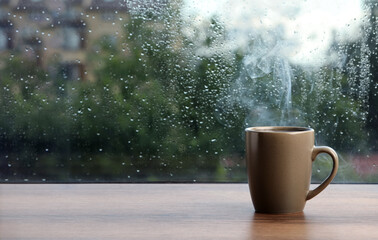 Cup of hot drink near window on rainy day. Space for text