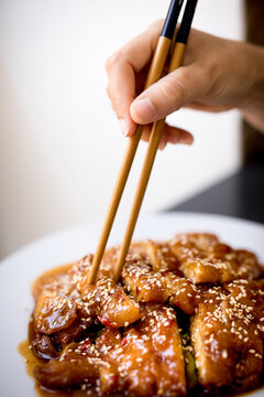 Crop hands taking spicy chicken on plate on wooden table