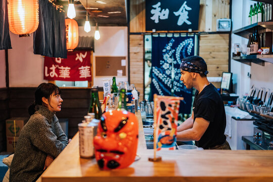 Asian woman and worker in bar