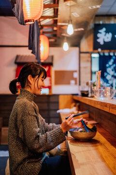 Asian lady in casual wear in cozy cafe