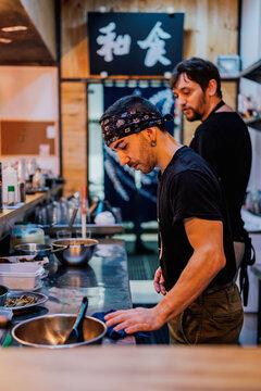 Professional man preparing dish in cafe