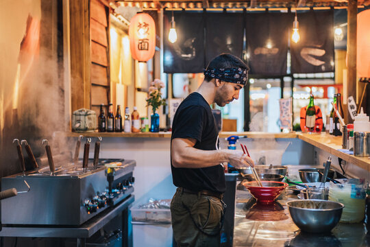 Man in bandana standing at counter and cooking ramen