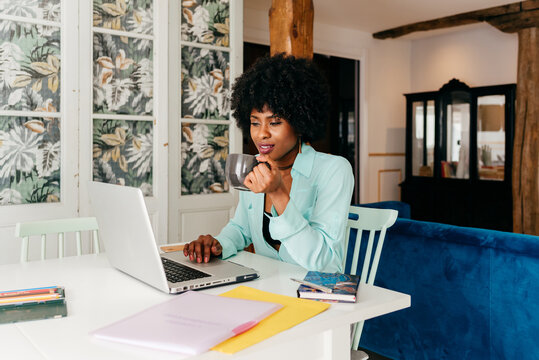 Black woman with cup of coffee working with laptop at home