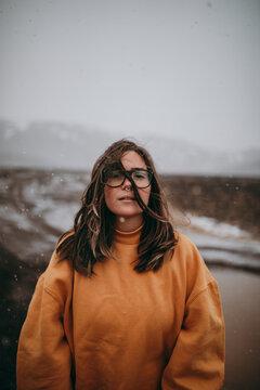 Smiling woman in eyeglasses on wild lands in snow