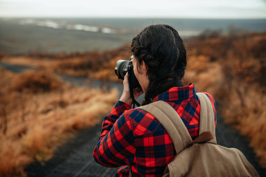 Young woman shooting on camera view from hill