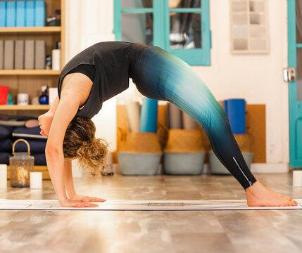 Flexible female doing Wheel pose in yoga studio