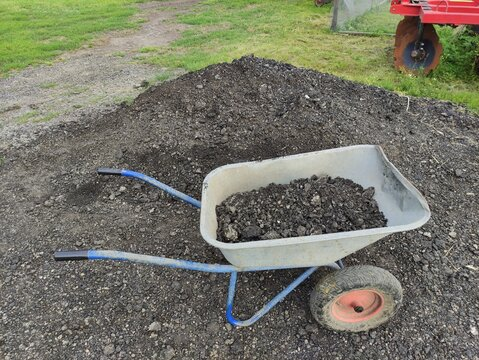 Wheelbarrow with stones, a coal or fertilizer and manure