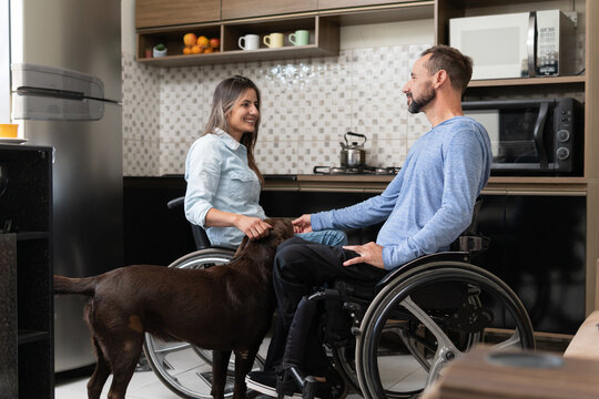 sweet couple in wheelchair and dog in kitchen.