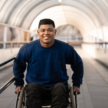 man in wheelchair finishing to climb tunnel ramp.