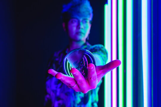 Woman spinning crystal ball in neon light