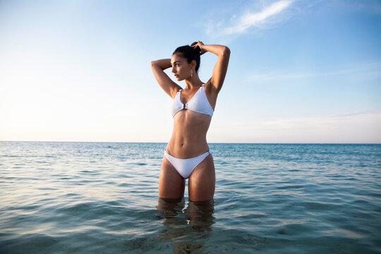 Model in swimsuit inside water on the beach