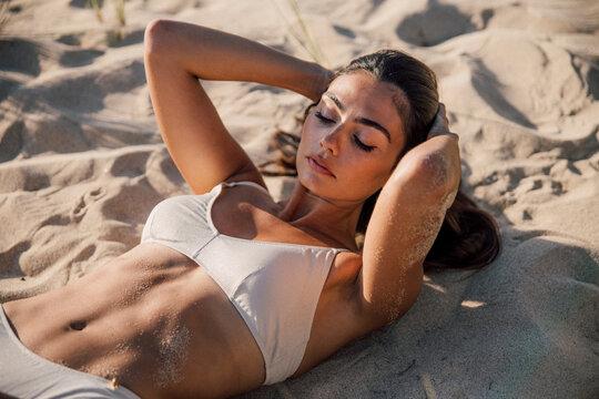 Gentle woman in swimsuit sunbathing on sandy shore