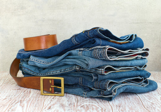 Folded jeans on wooden table close up