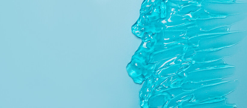 Skin care cosmetic product smear background.Transparent blue clear water gel surface texture with bubbles.